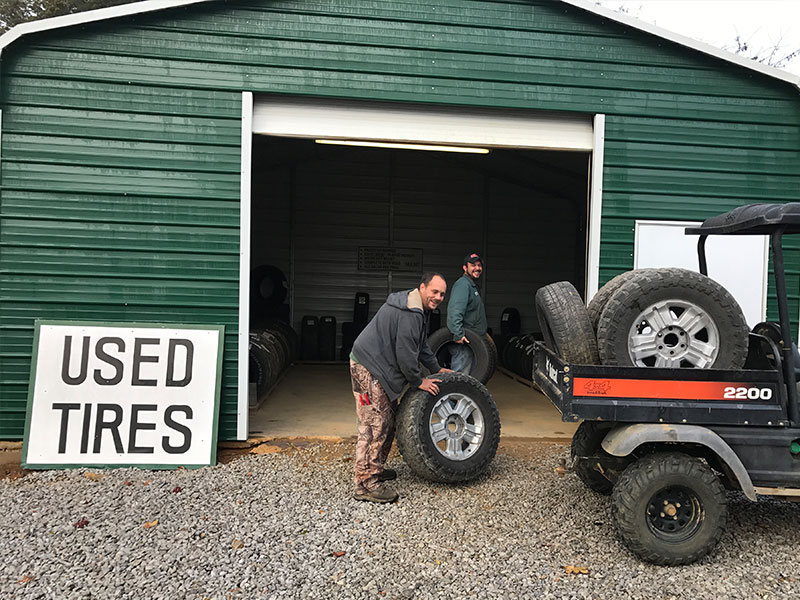 Britt (parts puller/dismantler) and David (inventory and parts manager) moving tires